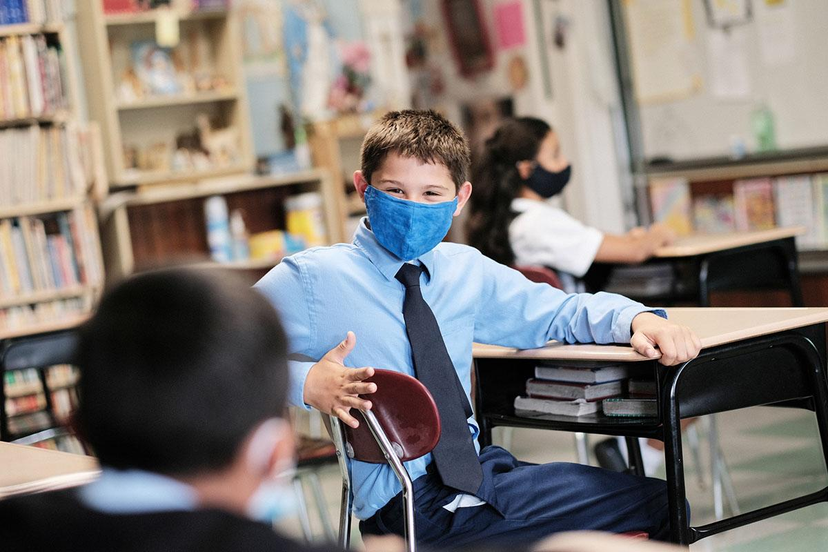 A student wearing a mask takes a break from studying at a Catholic school in East Boston