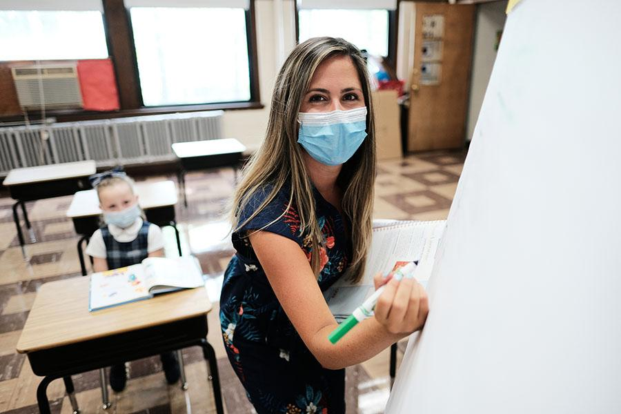 A teacher wearing a mask takes a moment from instruction in Haverhill, Massachusetts