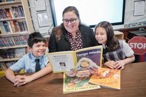 "Teacher Marybeth Forina reads ""Tengo Miedo"" to two students"